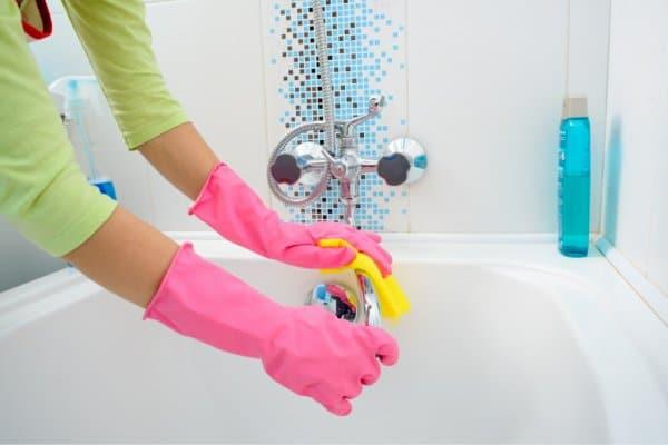 cleaning tub in bathroom