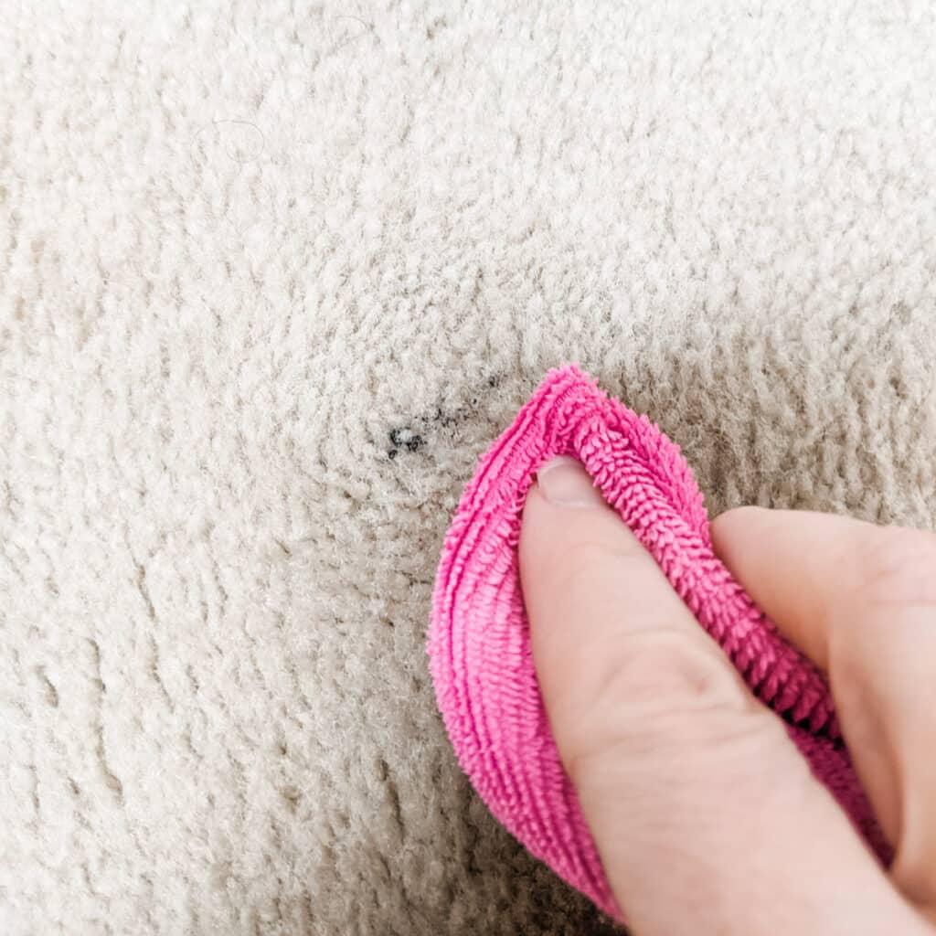 blotting away mascara stain on the carpet